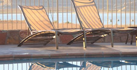 Dos tumbonas de jardín exterior junto a una piscina