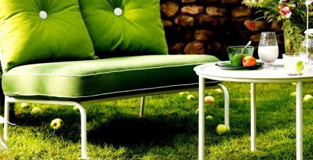 Un pequeño sofá verde en un jardin con decoración chill out de terraza